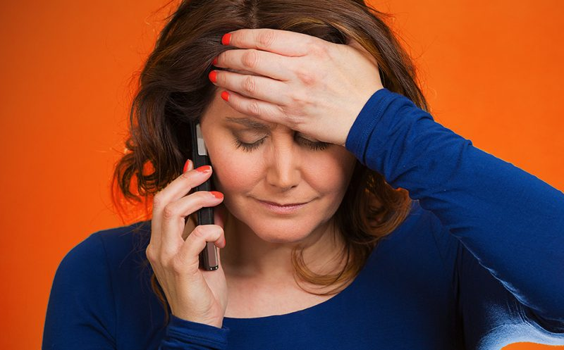 picture of lady holding phone with head in her hand looking frustrated