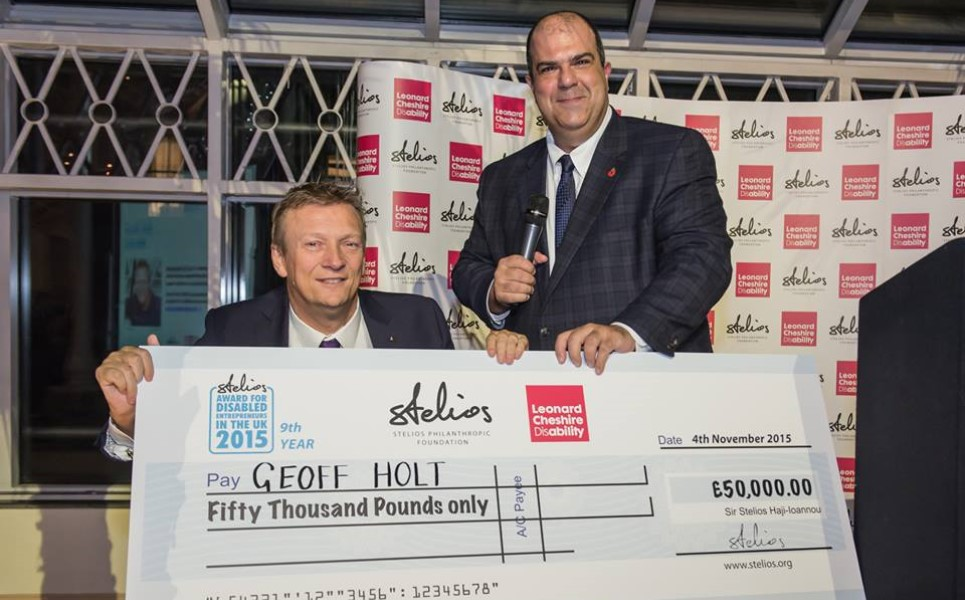 picture of stelios holding very large cheque for 50 thousand pounds payable to geoff holt